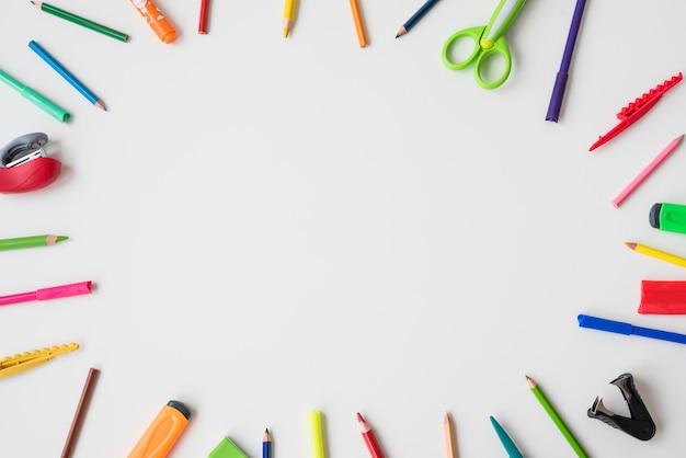 Material escolar, organizado em forma circular sobre o fundo branco