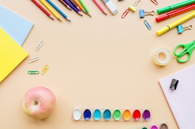 Material escolar, papelaria, lápis, tintas, papel em fundo laranja pastel