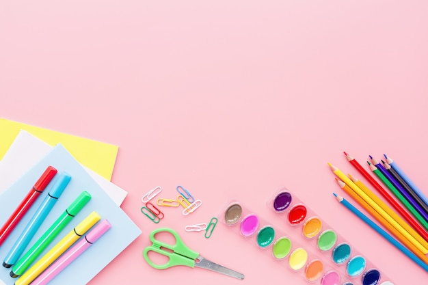 Material escolar, papelaria, lápis, tintas, papel em fundo rosa