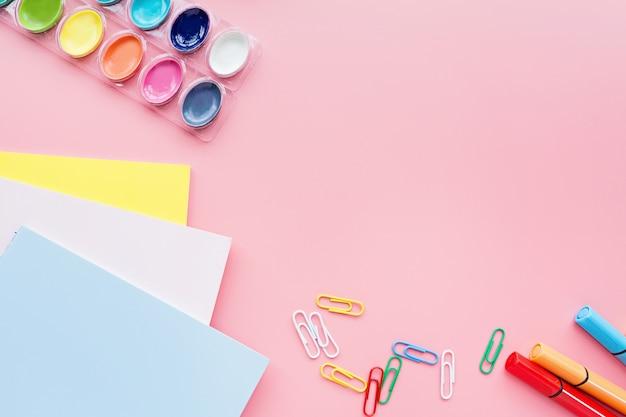 Material escolar, papelaria, tintas, caderno, clipes em fundo rosa