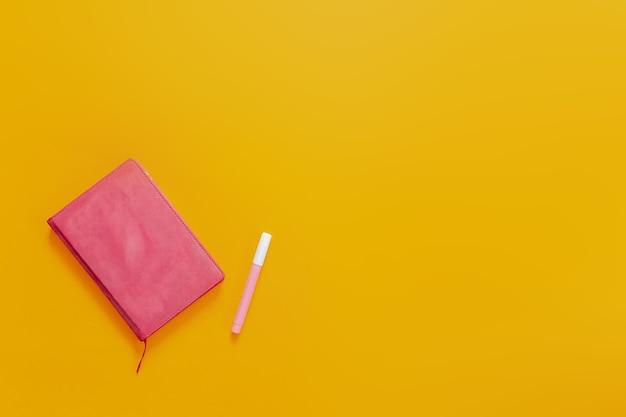 Material escolar plano deitar no fundo laranja. caderno rosa e canetas hidrocor e adesivos coloridos.