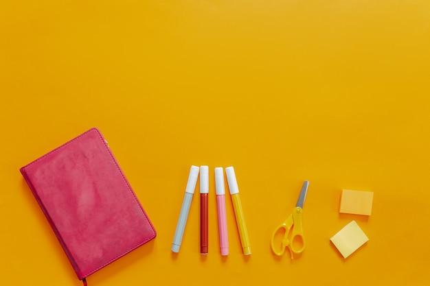 Material escolar plano deitar no fundo laranja. caderno rosa e marcadores coloridos, tesouras e adesivos.