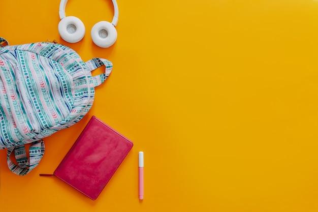 Material escolar plano deitar no fundo laranja. mochila azul, fones de ouvido brancos, caderno e canetas.