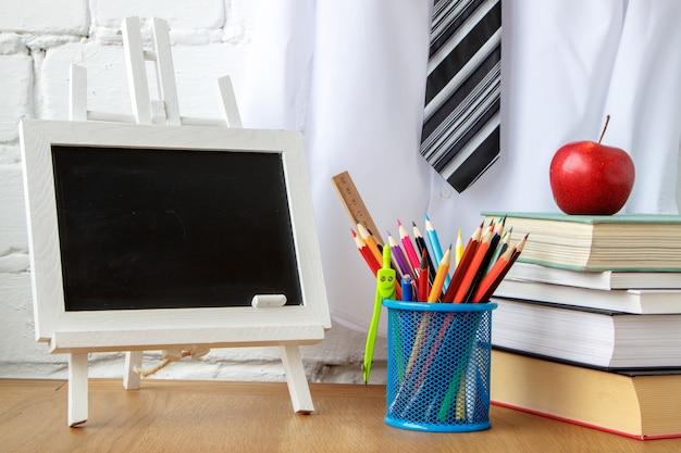 Material escolar, quadro de giz em miniatura, uma pilha de livros e uma maçã em cima da mesa