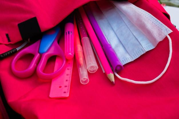 Material escolar rosa e máscara médica em uma mochila rosa. educação e volta ao conceito de escola.