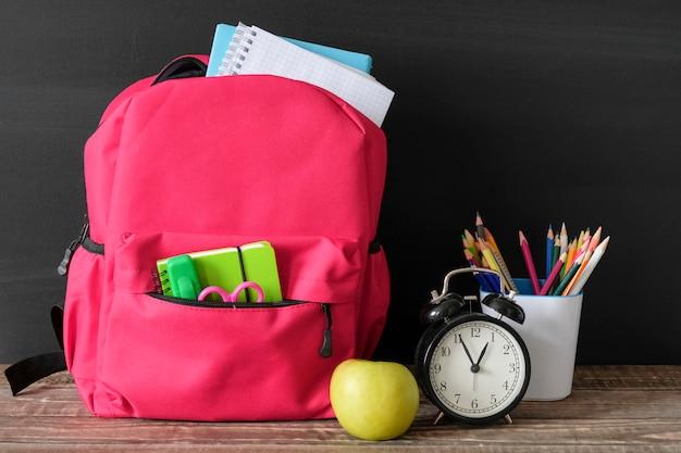 Material escolar, saco e papelaria na mesa de madeira no quadro-negro