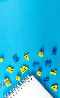 Material escolar sobre um fundo azul. conceito de dia de escola e professor. letras de madeira na mesa com espaço de cópia.