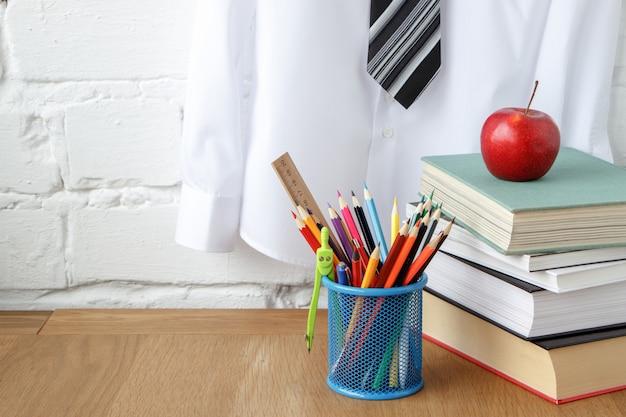 Material escolar, uma pilha de livros e uma maçã em cima da mesa