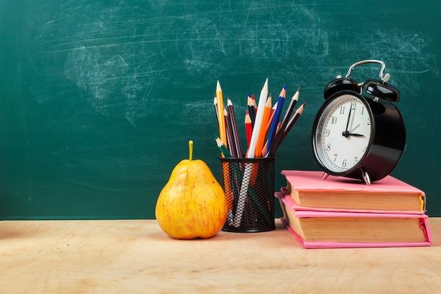 Material escolar. utensílios para escrever e despertador. hora de estudar o conceito