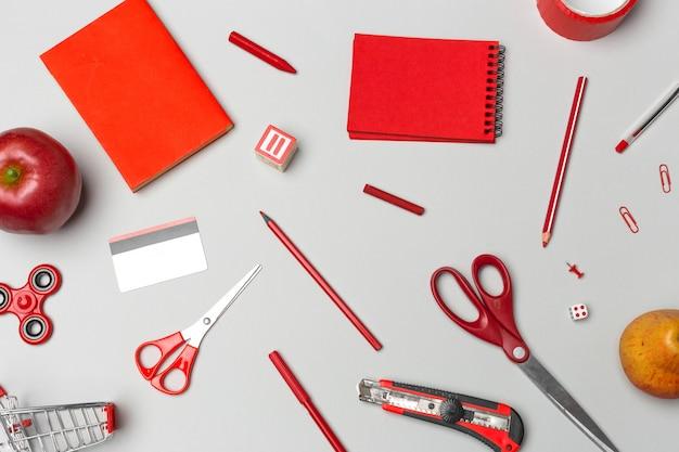 Material escolar vermelho no papel cinza