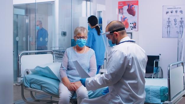 Material médico no visor explicando o resultado do x ray para uma velha aposentada sentada na cama do hospital durante a pandemia de covid-19. enfermeira verificando com o velho no fundo. clínica privada moderna ou centro de saúde
