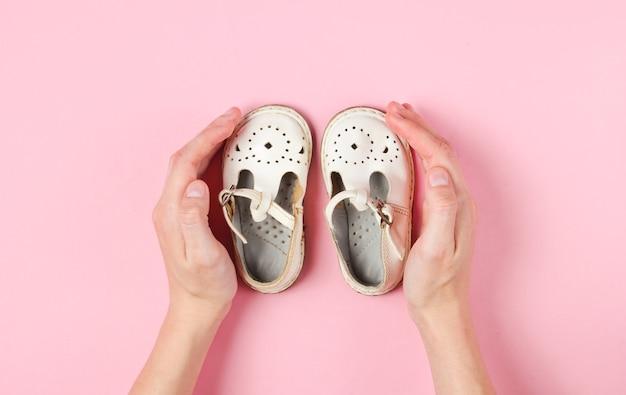 Maternidade, conceito de infância. mãos femininas abraçando sandálias de couro infantil em rosa.