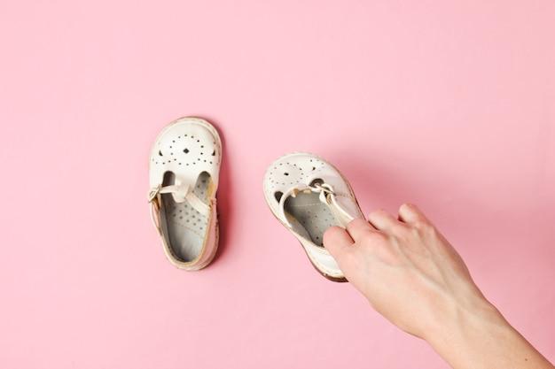 Maternidade, conceito de infância. mãos femininas segurando sandálias de couro infantil em rosa.
