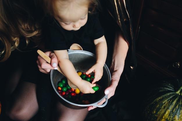 Matriz com a filha nos braços e está com as mãos entre os doces