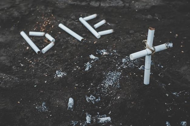 Matriz de inscrição no chão forrado de cigarros. túmulo de cigarros e cigarros com fumaça de tabaco. conceito anti-tabagismo. os perigos da nicotina para a saúde. fotos em tons escuros.
