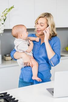 Matriz que fala no telefone móvel, mantendo seu bebê na cozinha