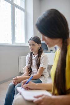 Mau humor. menina de cabelos compridos chateada olhando para o lado e sentada ao lado da psicóloga escrevendo