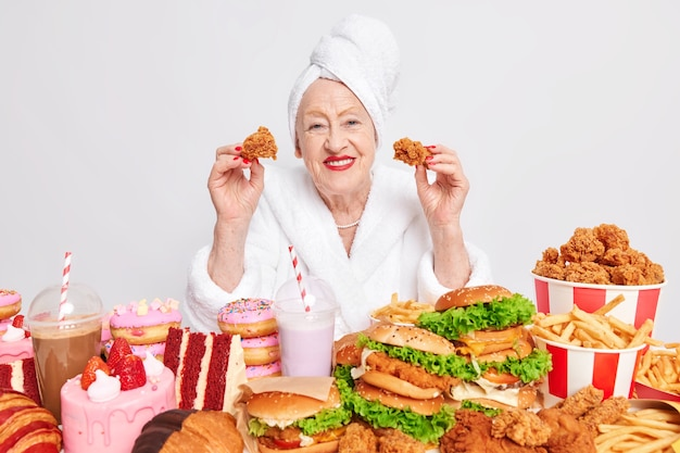 Maus hábitos alimentares. uma velha enrugada e feliz comendo junk food