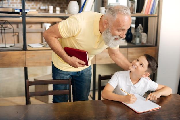 Me ajude. adorável menino de escola sentado à mesa e pedindo ajuda ao avô com uma tarefa de casa, enquanto sorri para ele com charme