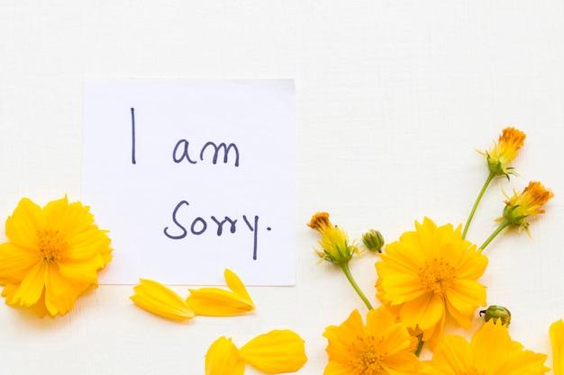 Me desculpe, mensagem manuscrita com flores do cosmos