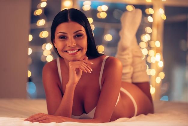 Me sentindo brincalhão esta noite. mulher jovem e bonita em lingerie e meias brancas deitada na cama e olhando para a câmera com luzes de natal ao fundo