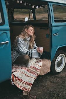 Me sentindo confortável. mulher jovem e atraente sorridente segurando uma caneca e desviando o olhar enquanto está sentado dentro da mini van azul estilo retro