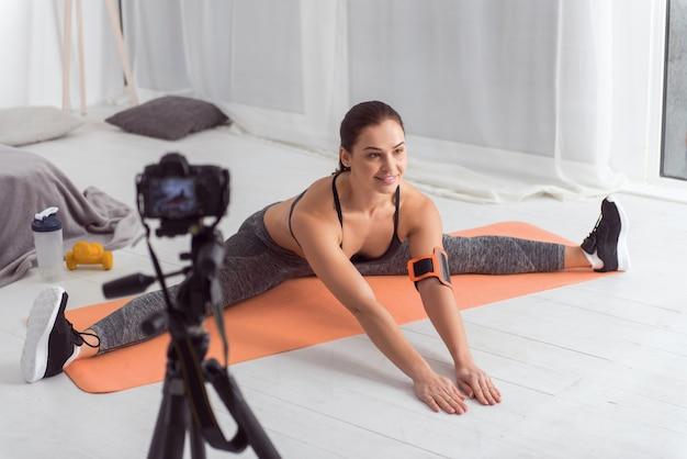 Me sentindo forte. mulher jovem de cabelos escuros bem parecidos e bem construídos, sorrindo e se espreguiçando enquanto está sentada no tapete e fazendo um vídeo para seu blog