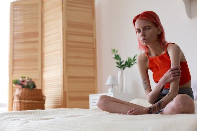 Me sentindo miserável. mulher ruiva anoréxica com tatuagens nos braços se sentindo péssima enquanto está sentada na cama