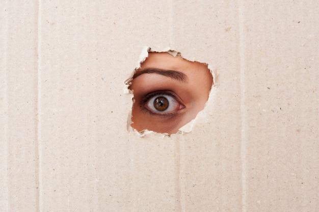 Me tire daqui! close do olho humano olhando por um buraco em um papelão