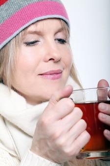 Meados de idade mulher com chá quente, vestindo roupas de inverno em um fundo branco