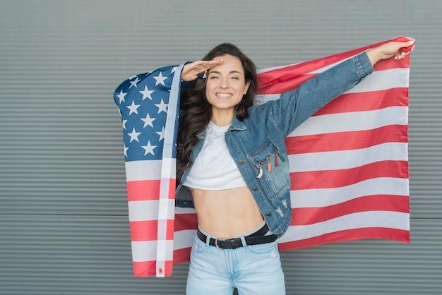 Meados de mulher tiro segurando grande bandeira eua e saudação de mão