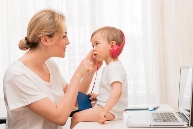 Meados de tiro bebê na mesa com fones de ouvido e mãe sorrindo