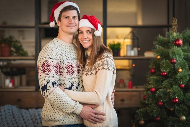 Meados de tiro casal vestindo blusas abraçando um ao outro