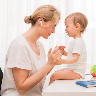 Meados de tiro feliz mãe e bebê, olhando um ao outro