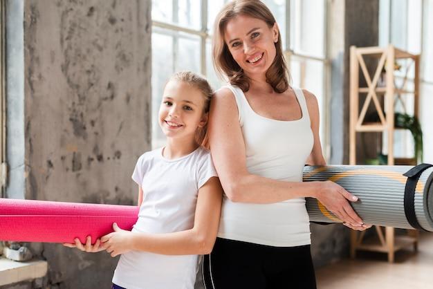 Meados de tiro feliz mãe e filha segurando tapetes de ioga