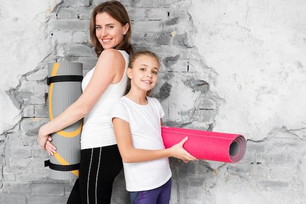 Meados de tiro mãe e filho segurando tapetes de ioga