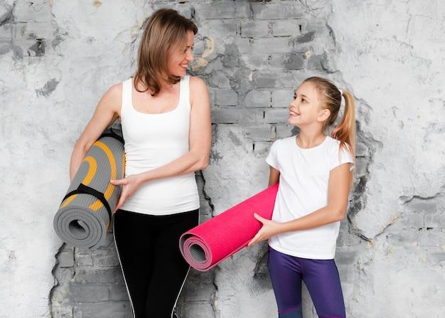 Meados de tiro mãe e menina segurando tapetes de ioga, olhando um ao outro
