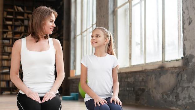 Meados de tiro mãe e menina sentada no tapete de ioga