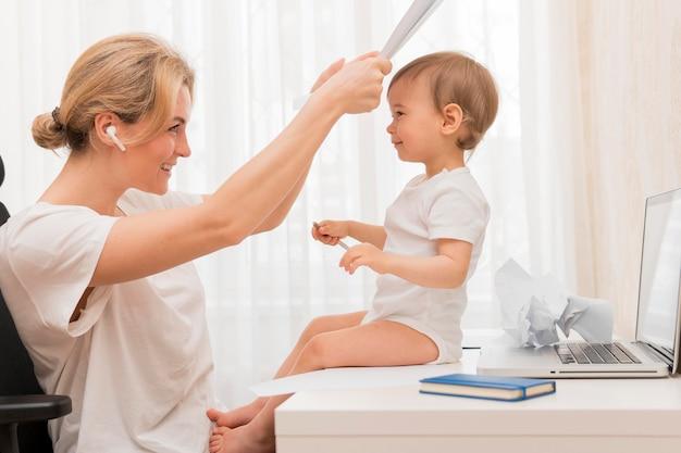 Meados de tiro mãe jogando espreitar uma vaia com bebê