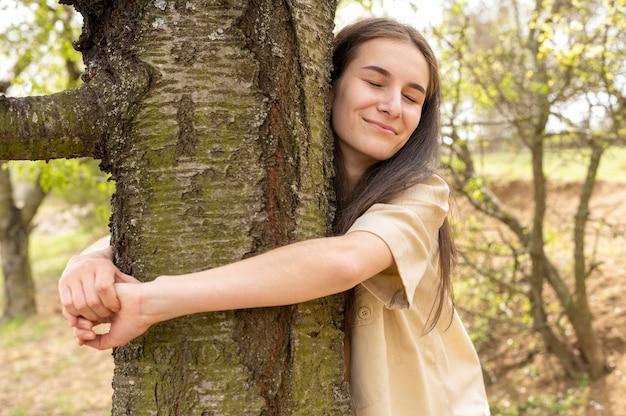 Meados de tiro mulher abraçando a árvore