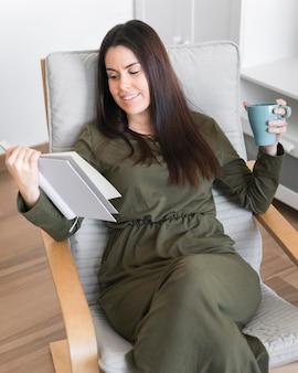 Meados de tiro mulher lendo livro e bebendo café