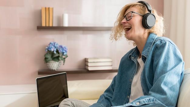 Meados de tiro mulher ouvindo música e bebendo café
