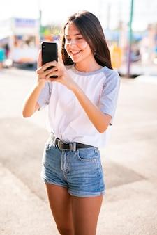 Meados de tiro mulher tirando foto com telefone