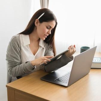 Meados de tiro mulher trabalhando em casa no tablet