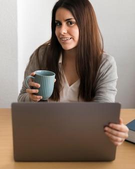 Meados de tiro mulher trabalhando no laptop e bebendo café