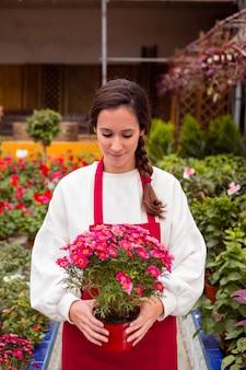 Meados de tiro mulher vestida com roupas de jardinagem, segurando o vaso de flores