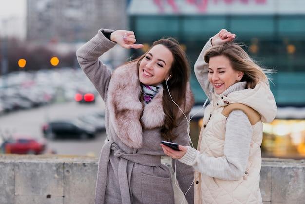 Meados de tiro mulheres sorridentes com fones de ouvido no telhado