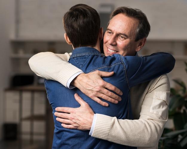 Meados de tiro pai e filho abraçando