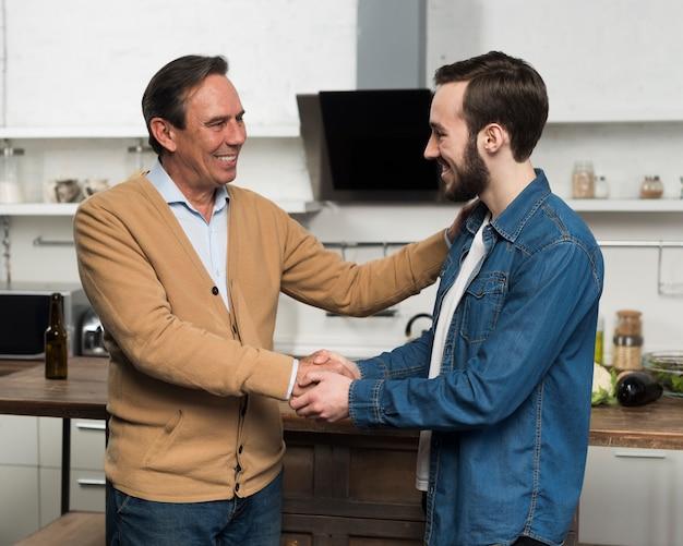 Meados de tiro pai e filho conversando na cozinha