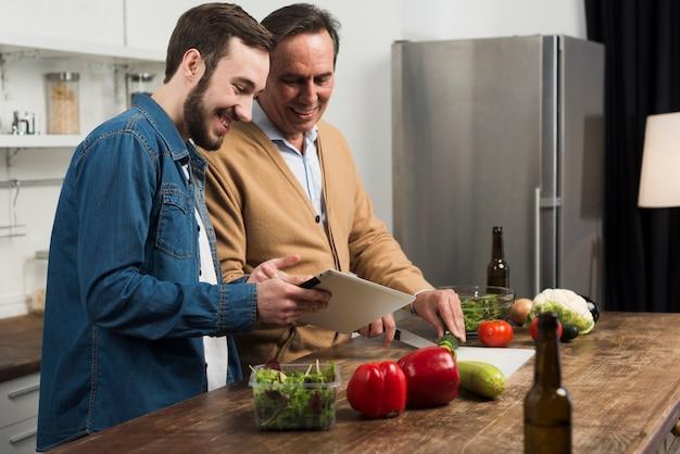 Meados de tiro pai e filho fazendo salada na cozinha